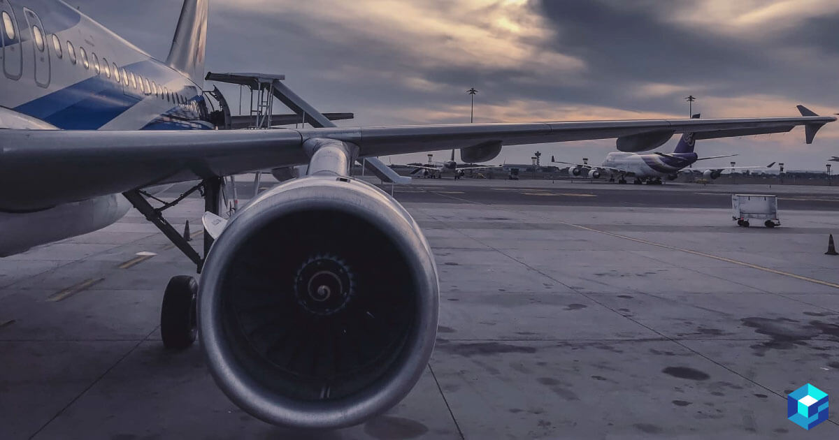 Picture of a commercial passenger plane jet and wing while it is parked on tarmac. Learn more about the component needs in civil aviation and see how Sourcengine can help you procure them.