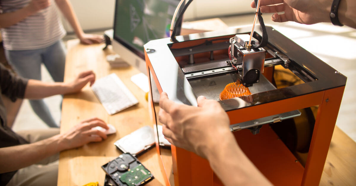 A 3D printer being used by a group of people. This is just one example of the acceleration of the 4th industrial revolution. Read more on Sourcengine about where the industry is going.