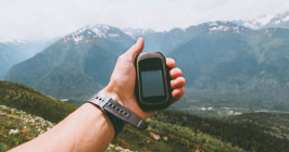 A hiker holding a GPS unit while navigating a mountain region; Unictron's Castle Patch Antenna is uniquely suited for GPS and other positioning devices; find out more at Sourcengine.