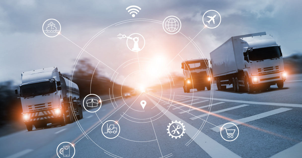 Cargo trucks driving with the sunset in the backdrop as the deliver component supplies to manufacturing companies; find out why supply chain professionals must digitize the chain now in 2020.