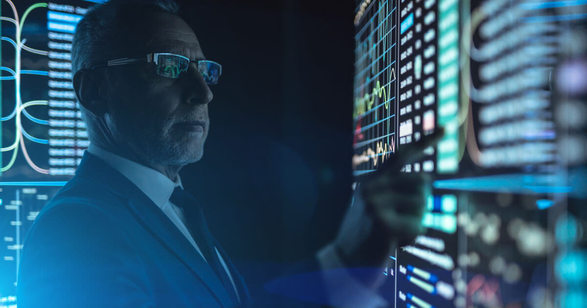 A CEO oversees a computerized board display telling him vital information about his company's supply chain; find out why CEOs must digitize the supply chain in 2020