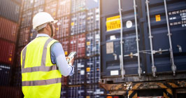 A supply chain professional overseeing cargo containers of components; find out how the coronavirus has impacted the supply chain at Sourcengine.