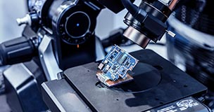 Microchip being produced under a power microscopic lens; passive and reactive component lead times have increased during the global chip shortage. Are you prepared? Try using sourcengine.com for all your sourcing needs.