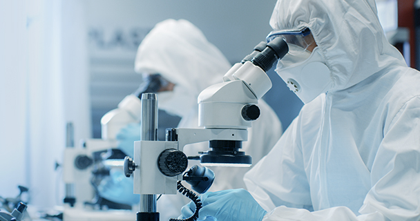 Two engineers in clean room suits look into microscopes inside a chip factory | Sourcengine