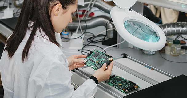 A worker inspecting a fully assembled PCB for flaws and signs of forgery within a laboratory setting.| Sourcengine
