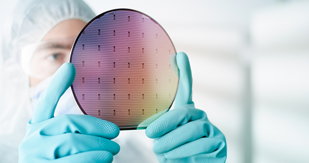 A worker in a clean room suit inspecting a test map for a silicon wafer at eye level | Sourcengine
