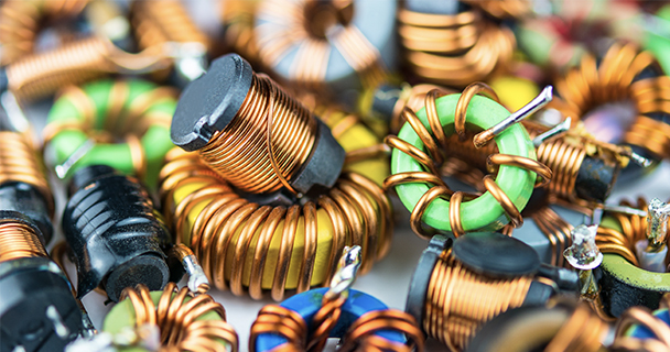 A closeup on a pile of inductors with copper winding and one with magnetic core.   Sourcengine