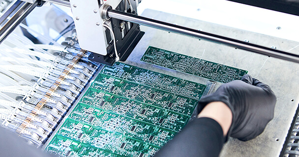 A gloved engineer tests a series of rectangular printed circuit boards in a laboratory environment. | Sourcengine