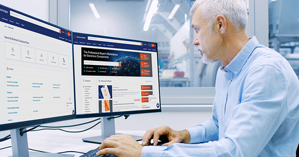 A man seated at a desk in an office environment looks at the Sourcengine homepage on his computer display.