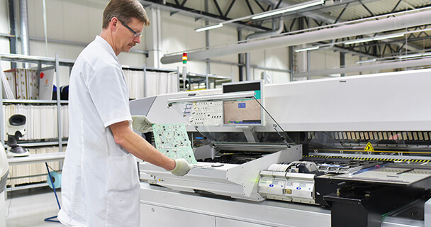 A man in a white coat holding a fully assembled PCB stands in front of a piece of manufacturing equipment. | Sourcengine