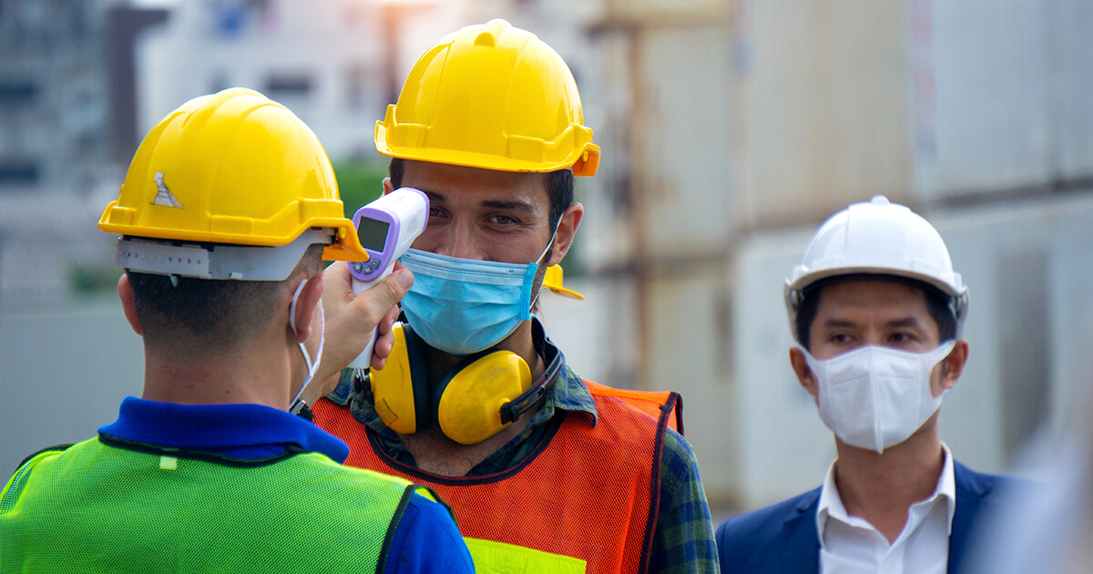 A worker performs a temperature check on another worker while a third observes.